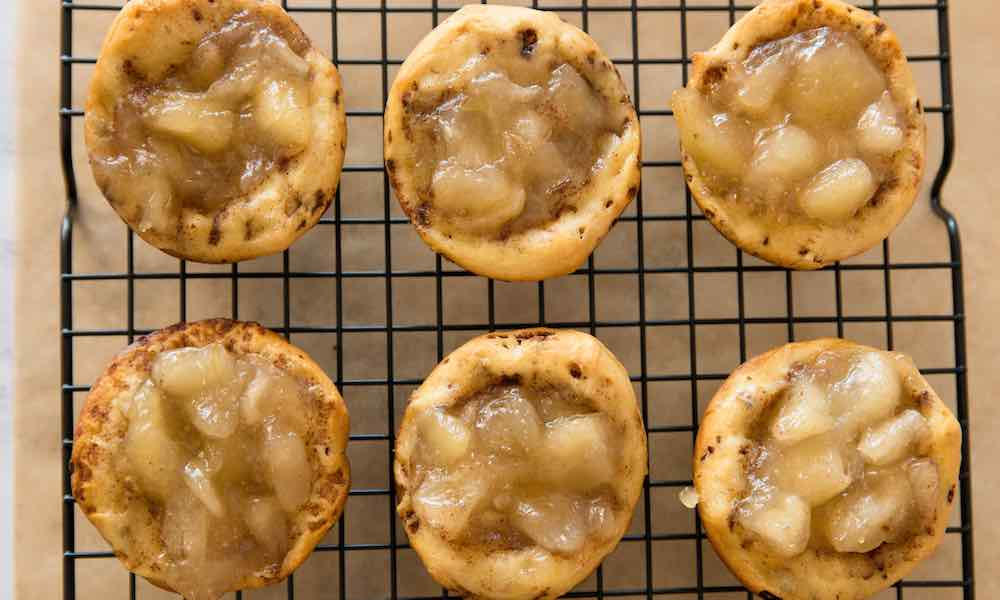 Apple Pie Cups with a cinnamon roll crust on a wire rack after baking