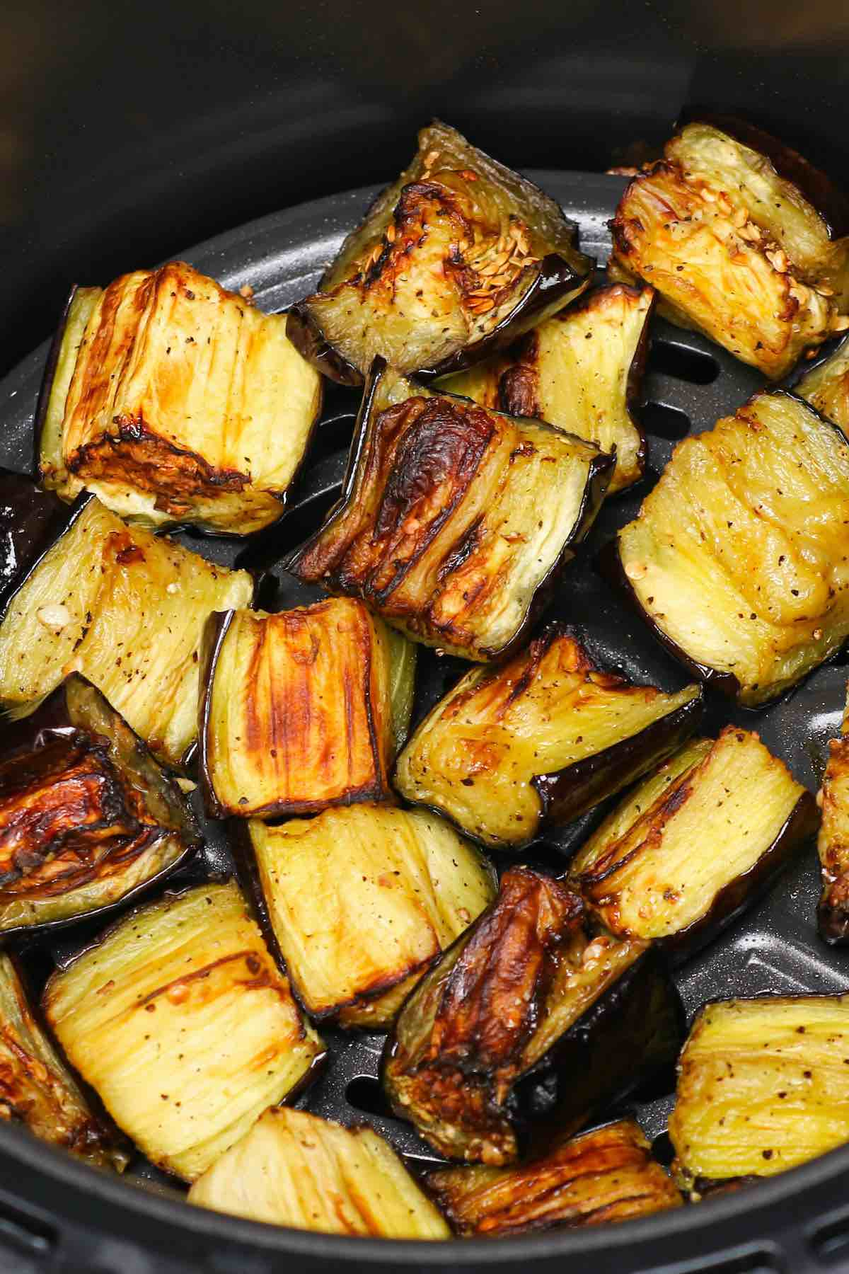 Beautifully caramelized pieces of seasoned eggplant in an air fryer basket #AirFryerEggplant