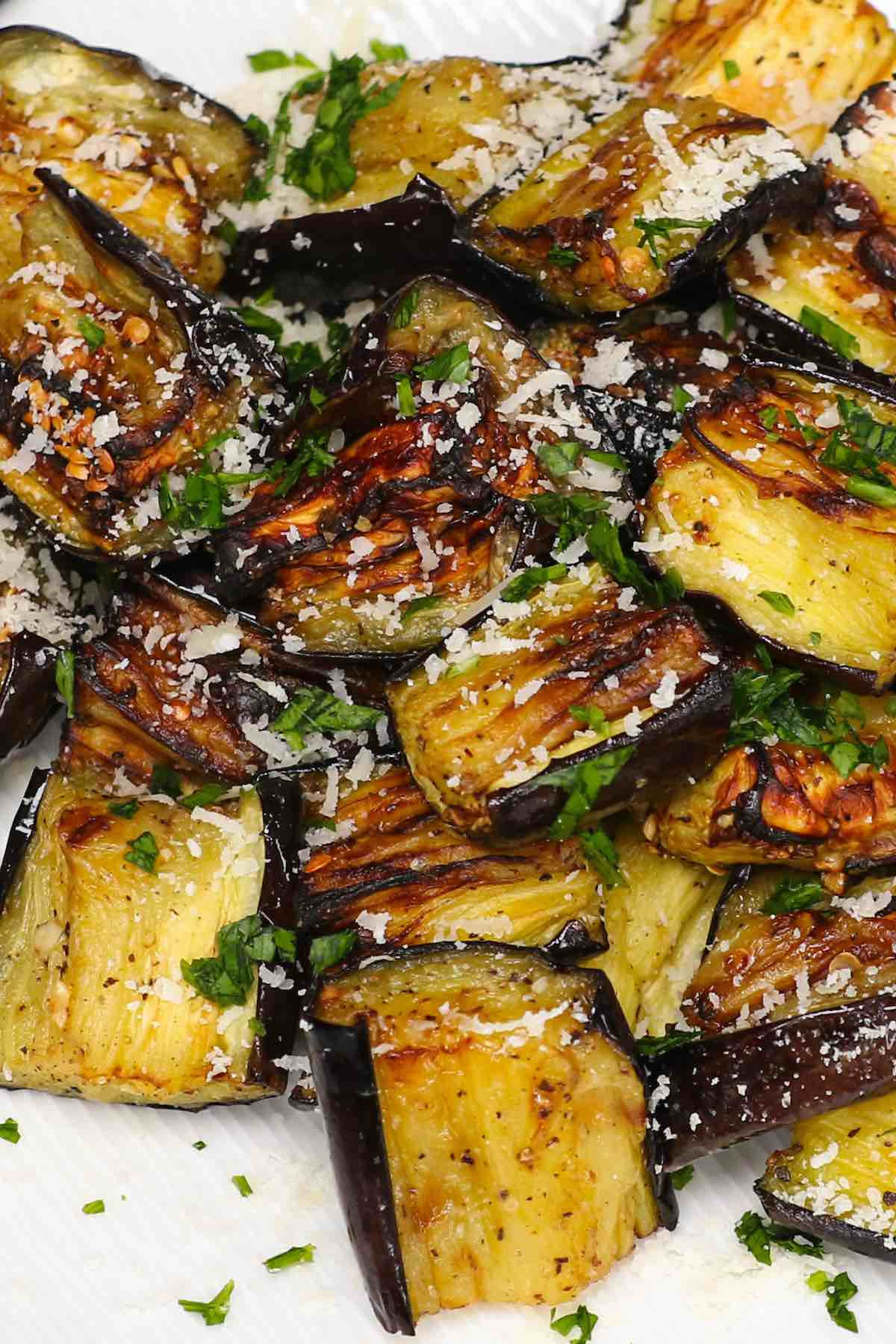Air Fryer Eggplant on a serving plate garnished with grated parmesan and parsley.