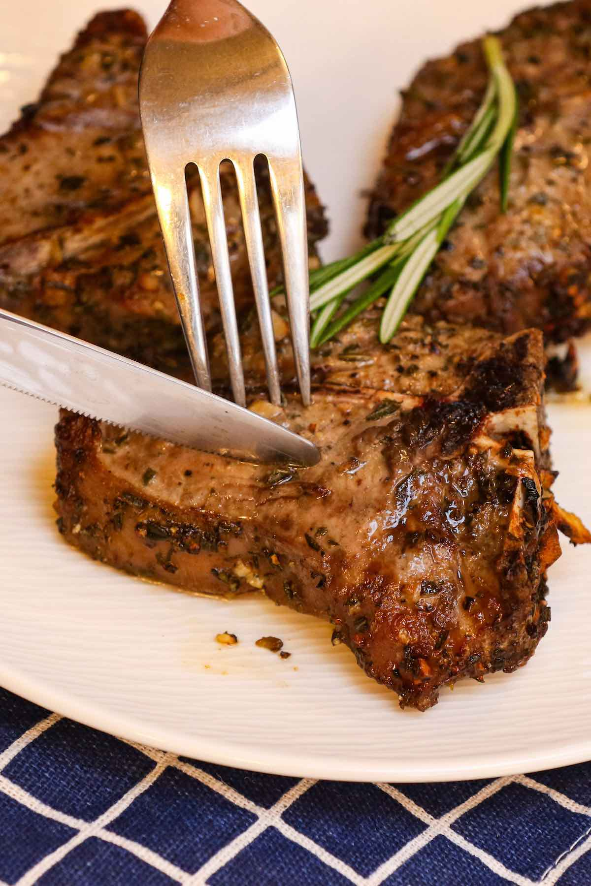 Cutting into a lamb loin chop with a fork and knife