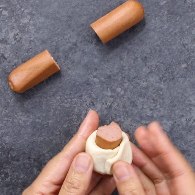 Chili Party Ring - this photo shows how to wrap pieces of hot dig in biscuit dough with your fingers