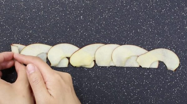 This photo shows how to roll thin apple slices together to make apple roses