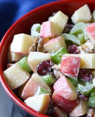 Crunchy apple salad in a serving bowl made with Fuji apples, walnuts, celery and cranberries