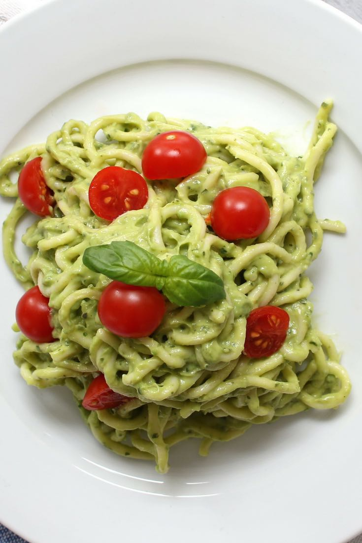 This is an overhead photo of Avocado Pasta on a plate with cherry tomatoes and basil on top