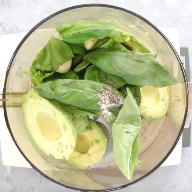This photos shows the ingredients for avocado pasta inside a food processor: avocados, fresh basil, garlic, salt and pepper