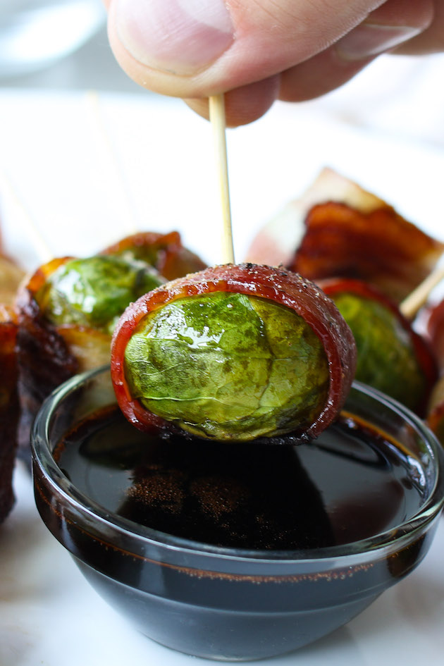A bacon wrapped brussel sprouts being dipped into a balsamic dressing for the perfect hors d'oeuvre