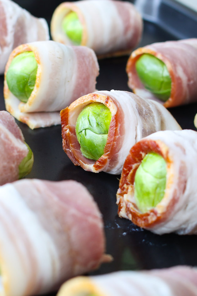 Brussel Sprouts wrapped in bacon on a baking sheet ready for baking