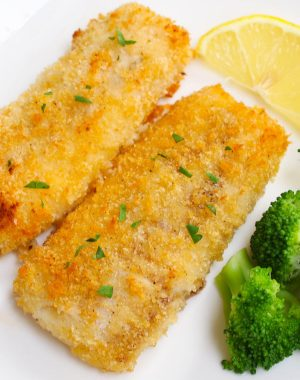 Baked breaded haddock fillets garnished with fresh lemon and served with a side of broccoli