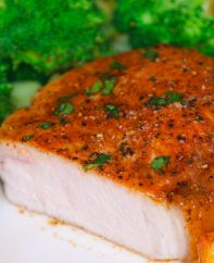 Cross-section of a baked boneless pork chop cut open on a serving plate with broccoli