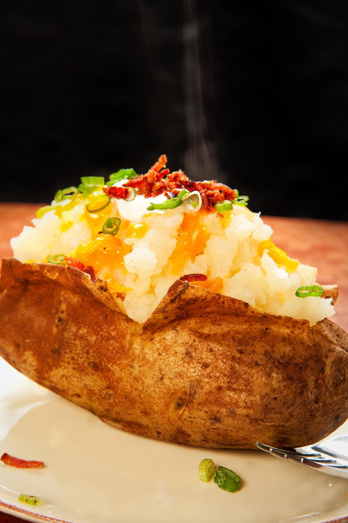 A fluffy baked potato with favorite toppings including butter, bacon bits and green onions