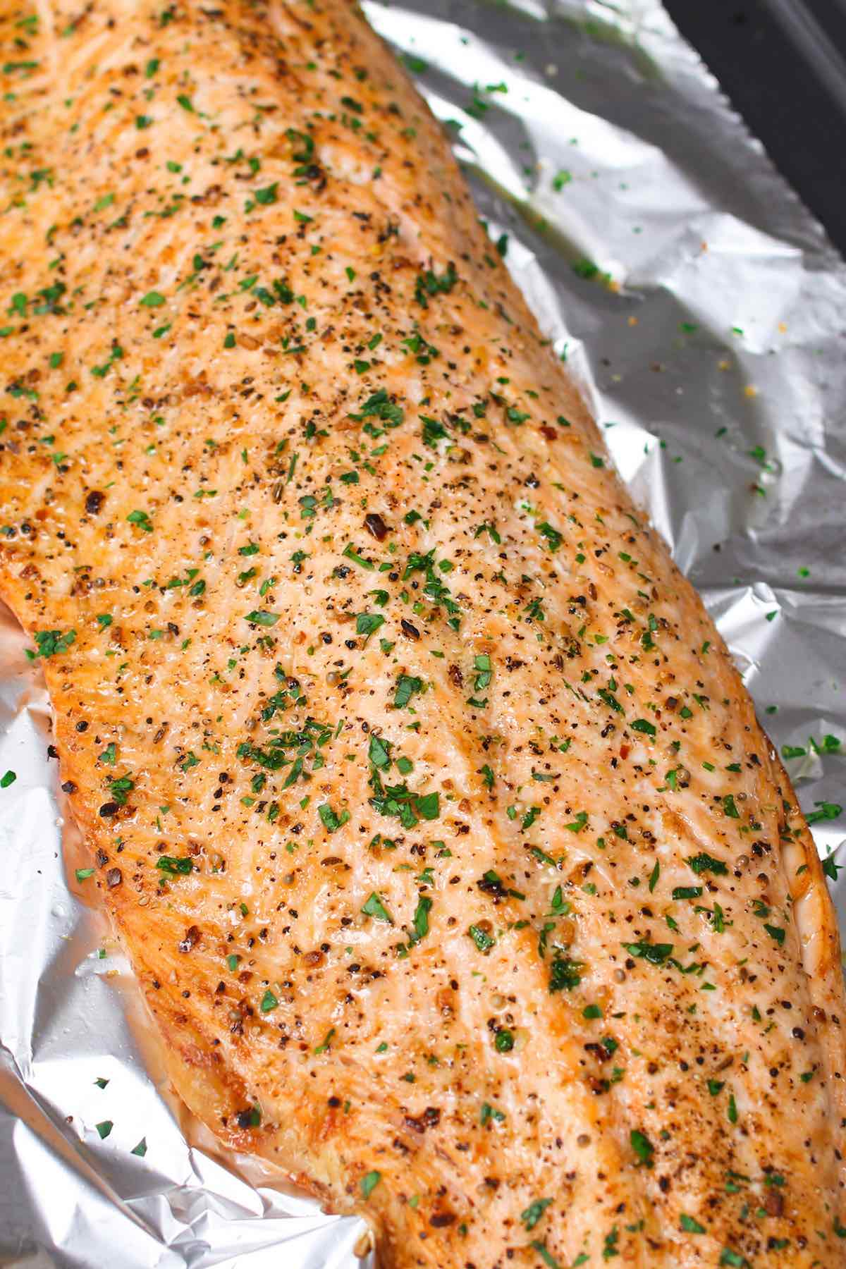 Baked Salmon fresh out of the oven with a crisp exterior and fresh herbs on top