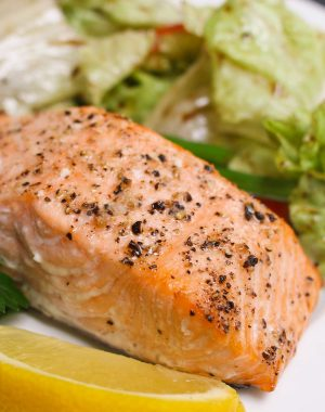 Serving of portion-size baked salmon fillet with a side salad on a serving plate with a lemon wedge