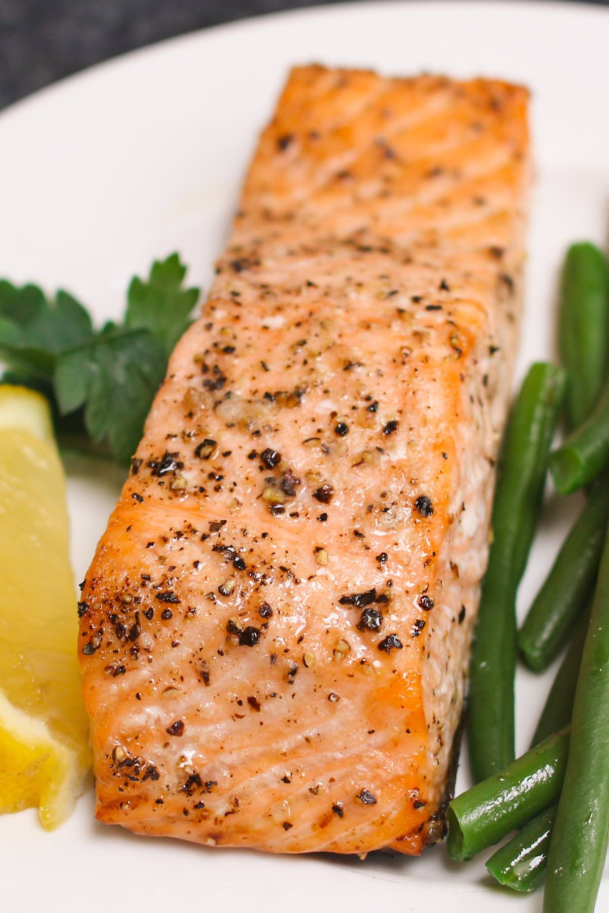 Center cut salmon fillet that's been baked to perfection featuring a golden exterior and served with green beans