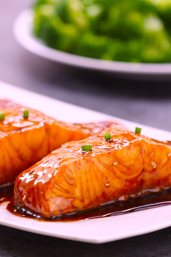 Closeup photo of center cuts of salmon on a serving plate after being baked with a simple 4-ingredient honey garlic sauce.
