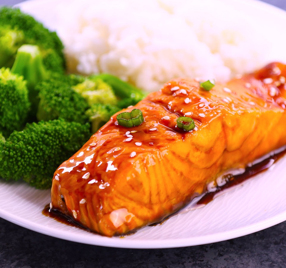 Gorgeous baked salmon glazed with a homemade honey garlic sauce on a serving plate with broccoli on the side for an easy weeknight dinner idea that's ready in about 20 minutes.