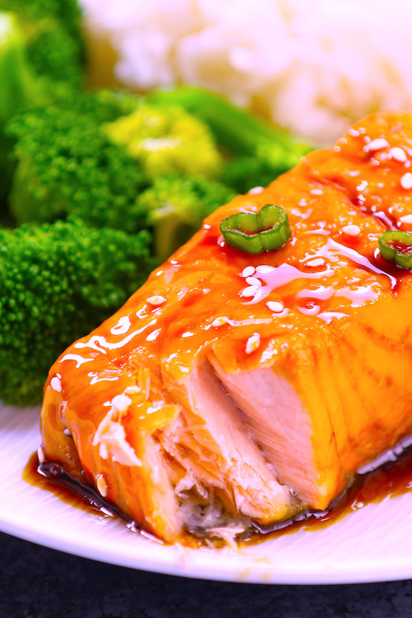 Closeup of salmon flaking after being baked to perfection with a honey garlic sauce.