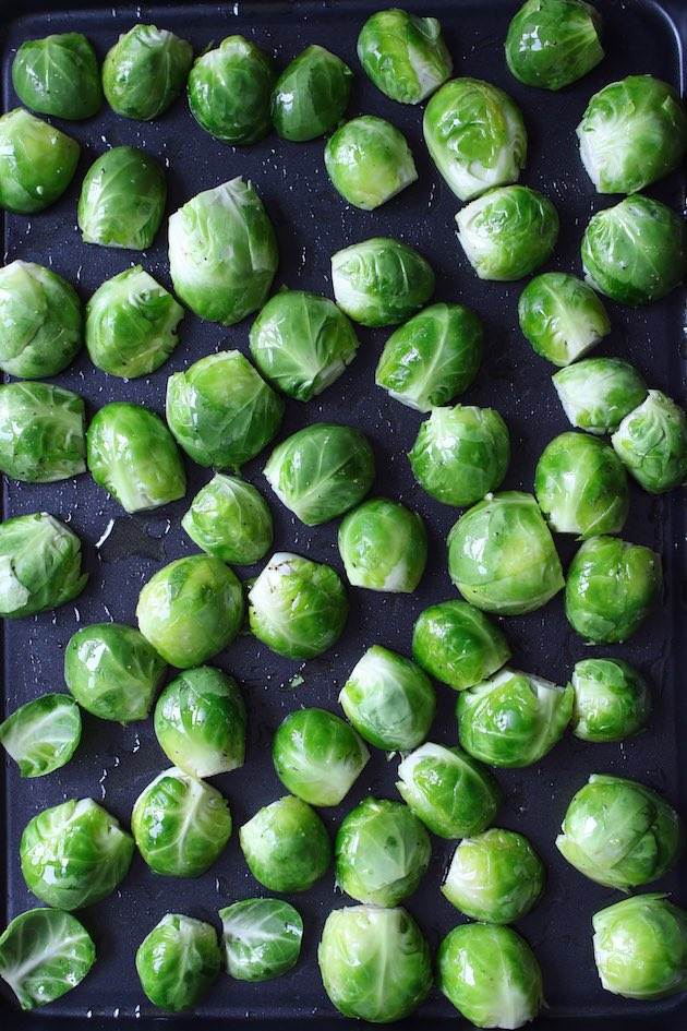 Brussel sprouts are placed into the sheet pan with a single layer with the flat sides facing down before roasting.