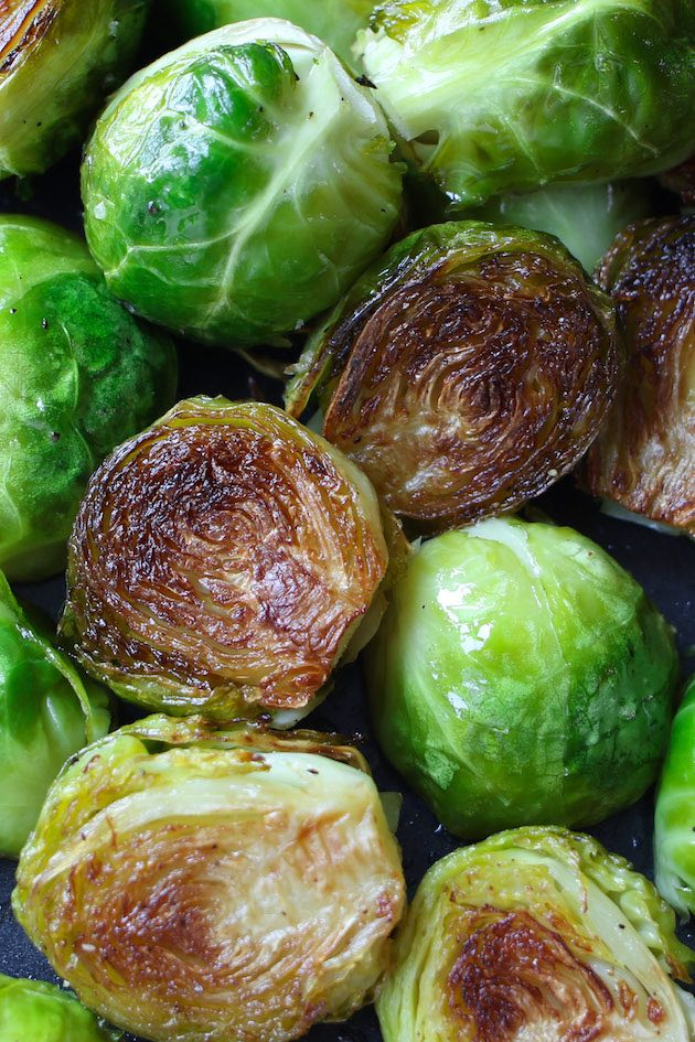 Brussel sprouts roasted to crispy perfection on a black sheet pan