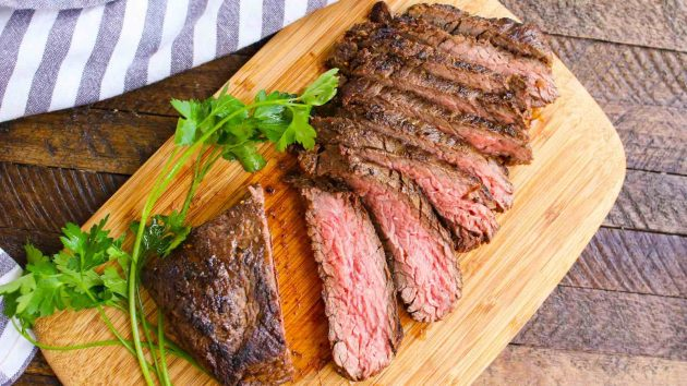 Sliced bavette steak on a carving board
