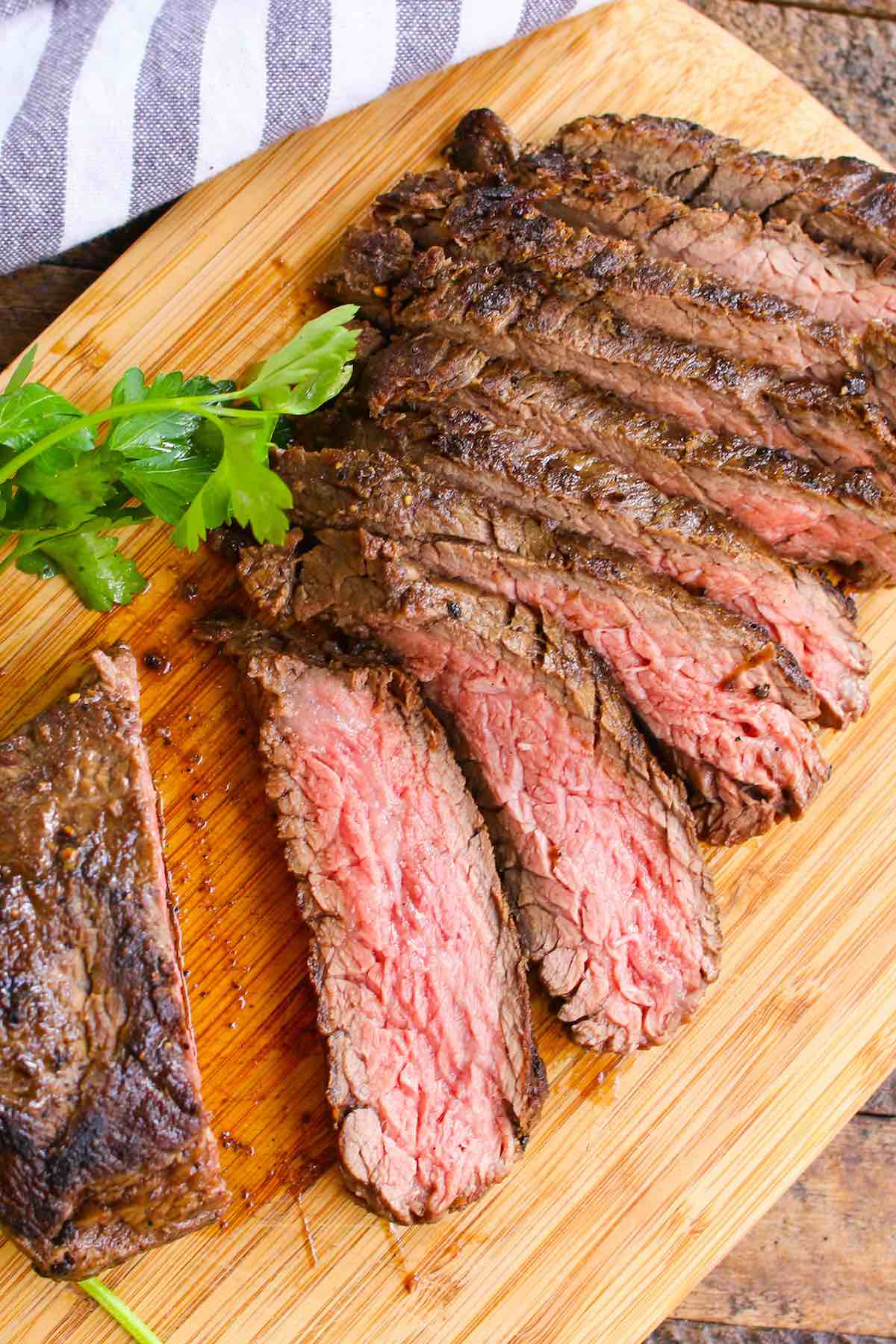Sirloin bavette steak cooked medium and sliced on a carving board showing a beautiful pink color
