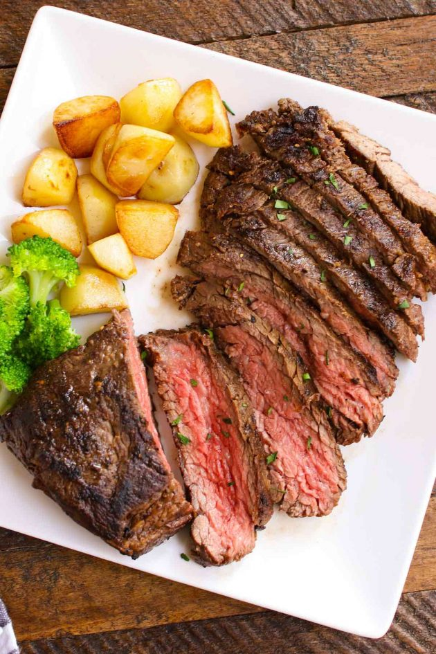 Sliced vacio steak on a serving plate with sautéed potatoes and broccoli