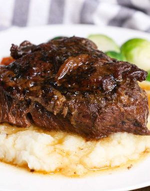 A braised beef cheek on a bed of mashed potatoes with Brussel sprouts