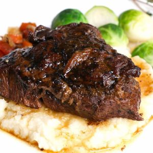 A serving of beef cheeks with mashed potatoes and vegetables