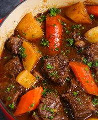 Homemade Beef Stew with carrots and potatoes cooked in a Dutch oven with fresh parsley on top