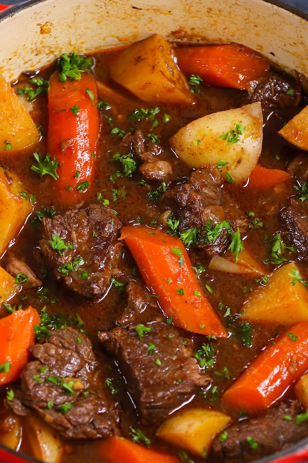 Closeup of chunks of beef, carrots and potatoes in a rich sauces with minced fresh parsley on top