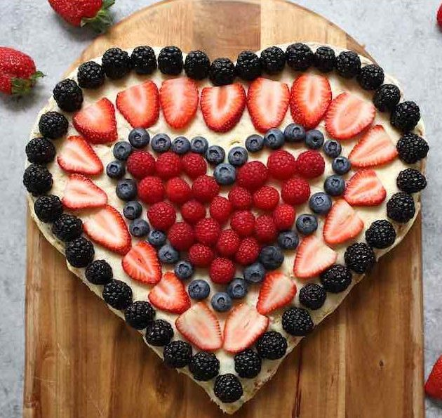 A Heart-shaped cake with fresh berries for a special occasion like Valentine's Day and Mothers Day
