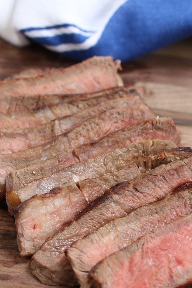 The best steak for tacos is flank steak, skirt steak, sirloin steak or rib eye steak. This photo shows thin slices of grilled sirloin steak cooked medium-rare and ready to be made into tacos