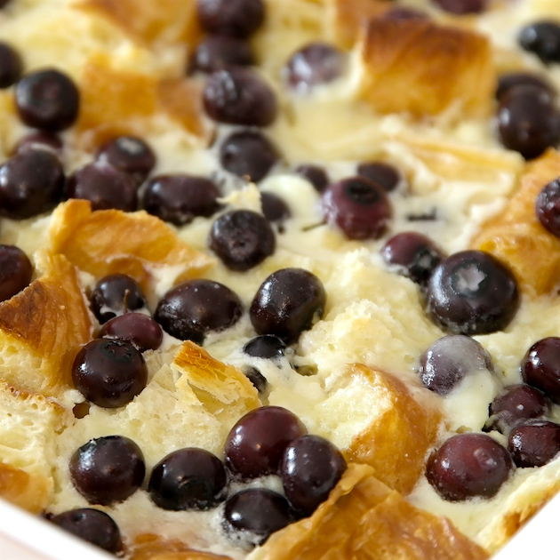 Blueberry bread pudding in a baking dish after coming out of the oven showing plump blueberries and a golden bread pudding surface