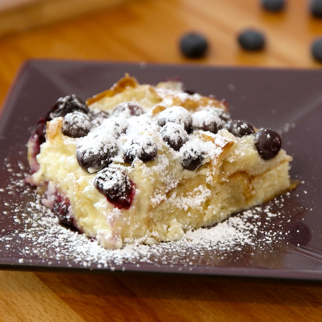 Blueberry Bread Pudding dusted with powdered sugar and served on a plate for a mouthwatering breakfast, brunch or dessert