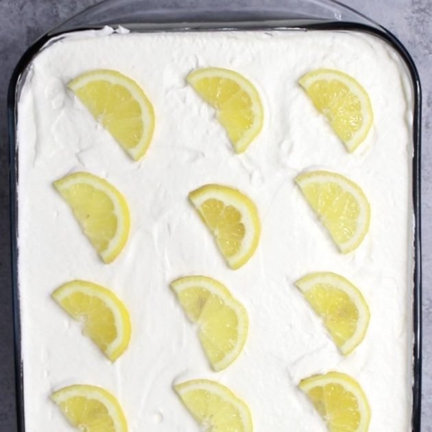 This is an overhead view of a Blueberry Lemon Poke Cake with lemon slices for decoration on top