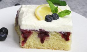 Blueberry Lemon Poke Cake – bursting with irresistible lemon and blueberry flavor. The lemon cake is poked with holes, and drizzled with lemony and sweet blueberry sauce, then topped with whipped cream. So Good! Perfect for a holiday party! Easy recipe. Vegetarian. Video Recipe | Tipbuzz.com