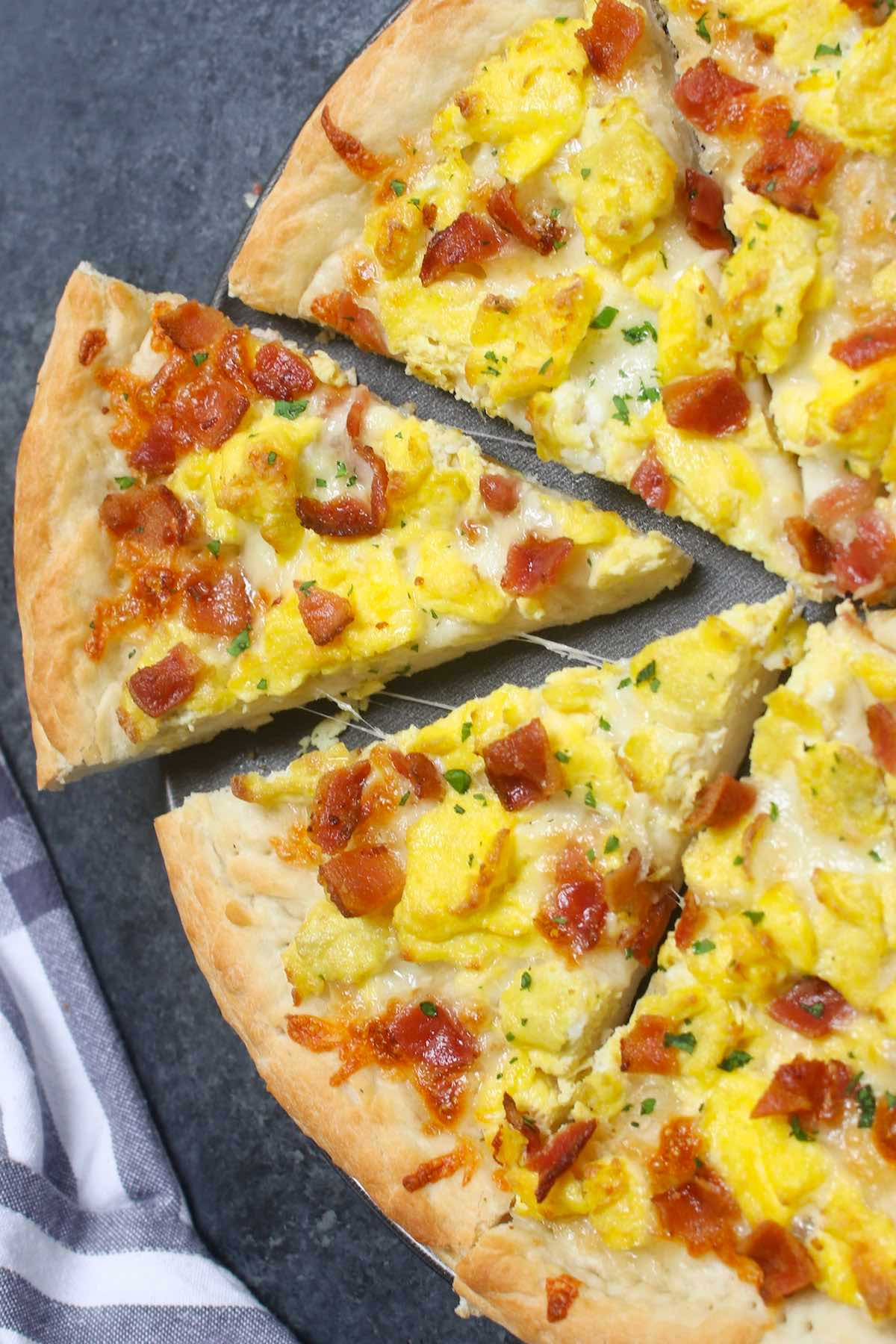 Easy Breakfast Pizza recipe begins with homemade pizza dough, topped with crisp bacon bits, scrambled eggs and mozzarella cheese.