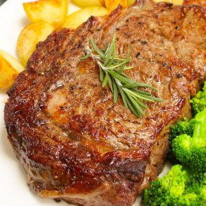 Perfectly broiled steak served with potatoes and broccoli on a serving plate with a sprig of rosemary for garnish.