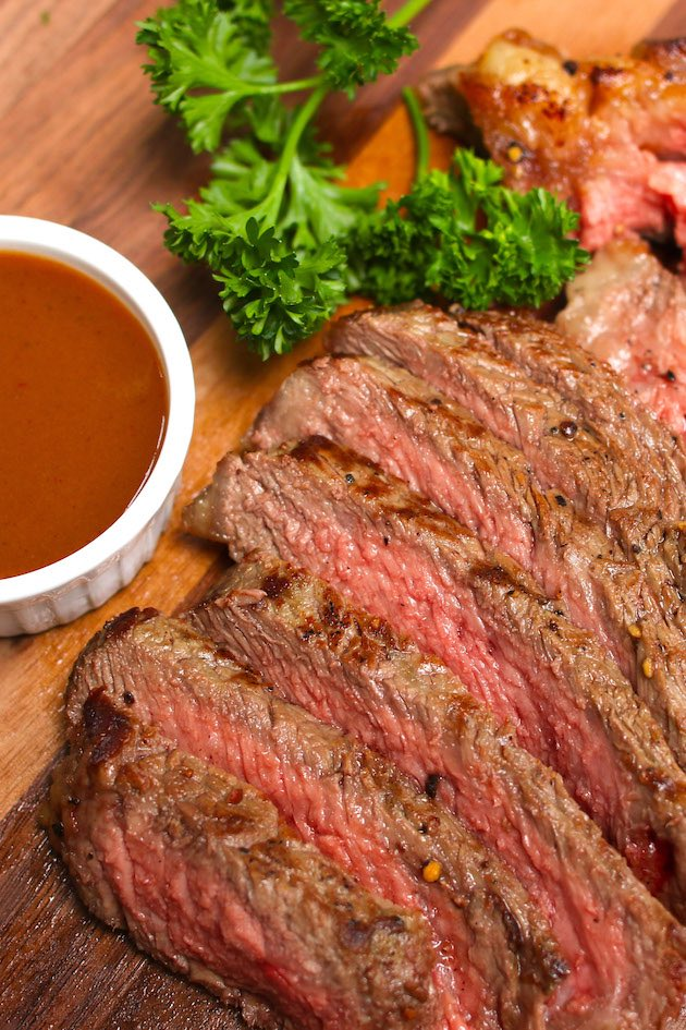 Beautiful broiled ribeye steak sliced thinly on a carving board with steak sauce and a sprig of parsley on the side