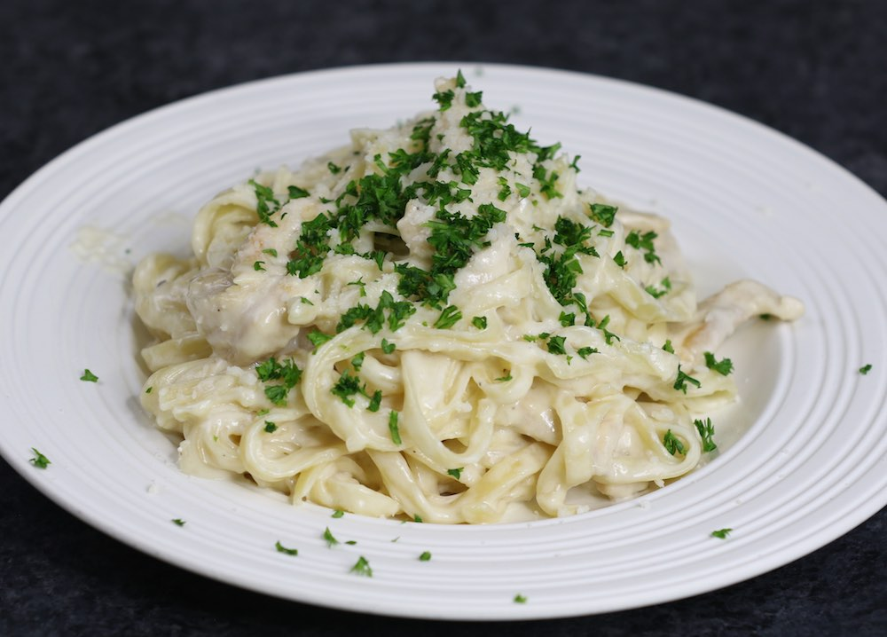 Chicken Alfredo on a serving plate garnished with minced parsley