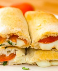 This Calzone Recipe will take your Italian favorite to a new level - loaded with sausage, peperoni, mozzarella, ricotta, Parmesan cheese and vegetables wrapped with soft and fluffy calzone dough. These cheesy Calzones make perfect weeknight dinner. Tipbuzz.com #Calzones #CalzoneRecipe