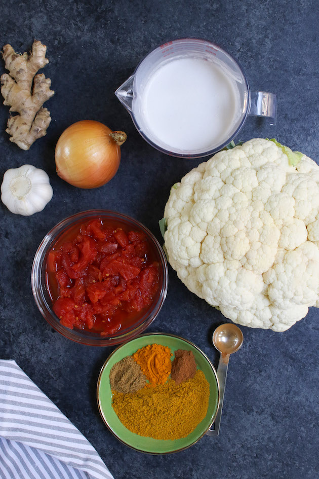 All ingredients displayed on the counter: coconut milk, cauliflower, ginger, onion, garlic, diced tomatoes, yellow curry powder, turmeric, cinnamon and cumin