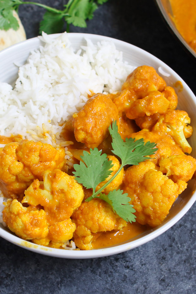 Cauliflower curry served on rice in a white bowl