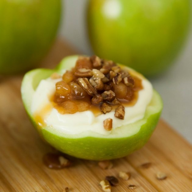 A half apple filled with cheesecake and topped with toasted pecans and caramel sauce