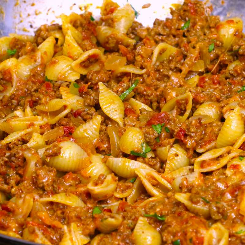 This is a closeup photo of cheesy taco pasta made with small shell pasta in a skillet