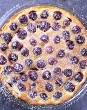 Overhead view of a freshly baked cherry clafoutis dusted with powdered sugar