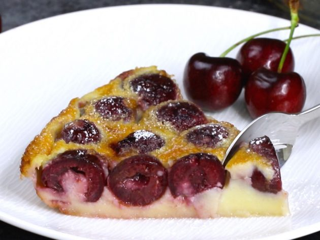 A wedge cherry clafoutis on a serving plate with fresh cherries on the side