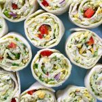 Chicken Avocado Salad Roll Ups – Ready in 15 minutes and it's a guaranteed hit with family and friends. All you need is some simple ingredients: Shredded chicken, avocado, plain yogurt, lime juice, red onion, red bell pepper, green onion, cheddar cheese, parsley and flour tortillas. So yummy! Perfect for a summer time party or a picnic. Quick and easy recipe. Lunch or side dish. Video recipe. | Tipbuzz.com