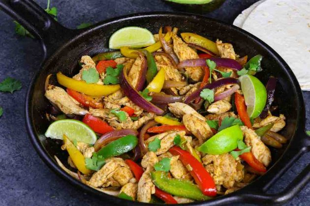 A cast iron pan with thin strip of chicken, bell peppers and onions ready to serve