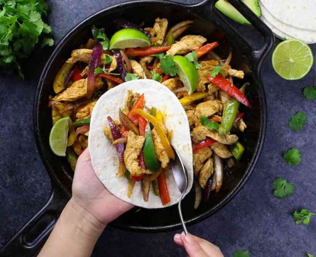 Assembling chicken fajitas on a tortilla