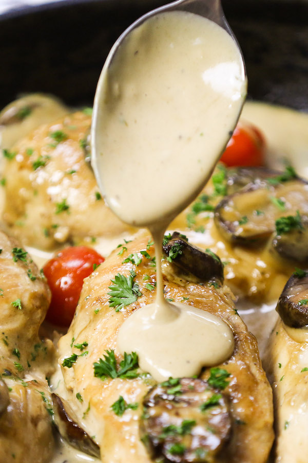 Creamy Chicken Marsala - this is a closeup view of spooning creamy marsala onto cooked chicken in the pan after cooking